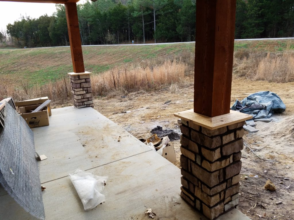 Wooden front porch posts with the stone work.