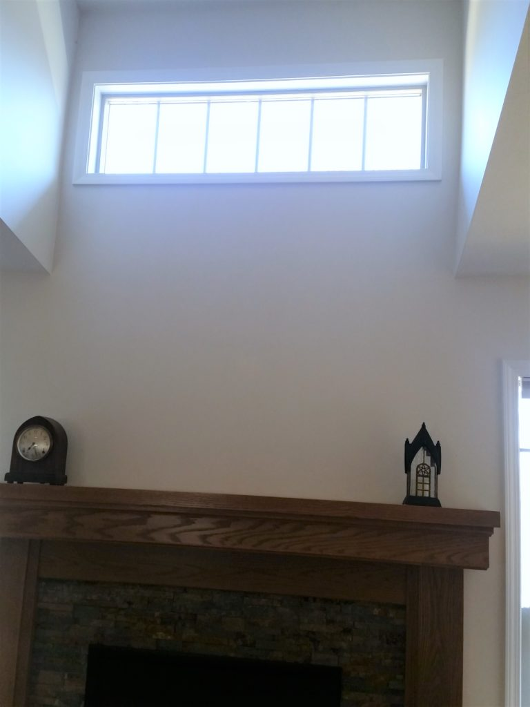 A closer view of the high window above the fireplace.