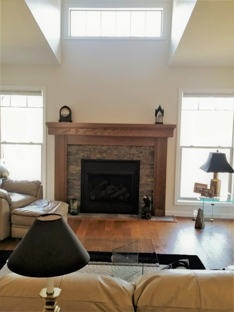 A view of the family room, fireplace, and high window.