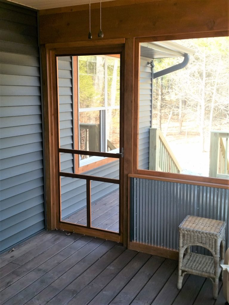 A view of the outside door from inside the screened-in porch.