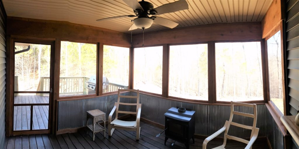 A panoramic view of the inside of the screened-in back porch.